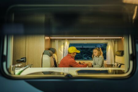 Family RV Camper Trip. Caucasian Father and Daughter Playing Inside Motorhome. Seating in Dinette Section. Summer Road Trip. Stock Photo