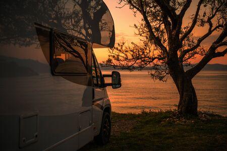 Recreational Vehicle Camper Van RV Park Site Scenic Sea Front Sunset. Motorhome Road Trip. Stock Photo
