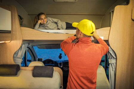 Caucasian Men in His 30s and His Daughter Inside Camper Van Motorhome Preparing RV For the Bed Time. Transportation and Travel Industry.