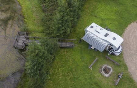 Modern RV Class C Camper Van Parked on Beautiful Camping Spot with Access to Small Pond. Aerial Photo.  Stock Photo