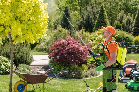 Seasonal Garden Fertilization by Caucasian Gardener with Professional Equipment. Gardening Theme.