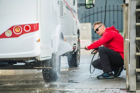 Detailed Camper Van RV Cleaning After Active Summer Season. Caucasian Men Washing His Motorhome Using Pressure Washer.  Stock Photo