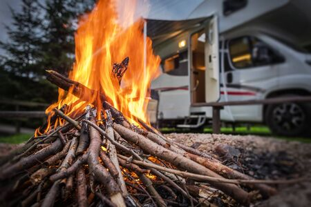 RV Park Campfire in Front of Motorhome Pitch. Summer Camping with Motorhome. Stock Photo