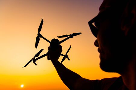 Men Flying Small Drone During Sunset. Aircraft in a Hand. Industrial Theme.