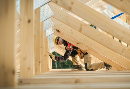 Caucasian Contractor Working with Wooden House Frame in the Attic Section.  Stock Photo