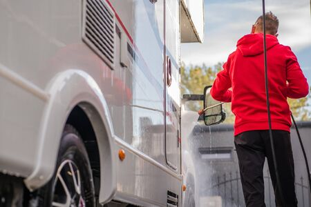 Men Cleaning His Camper Van Motorhome in a Car Wash Using Pressure Washer. Stock Photo
