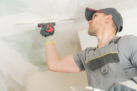 Caucasian Contractor in His 30s Patching Drywall Walls. Construction Site.