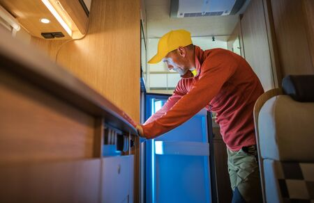 Caucasian Men in His 30s Looking Inside RV Camper Van Refrigerator. Motorhome Appliances.