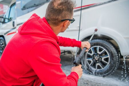 RV Owner Taking Care of His Camper Van. Motorhome Pressure Washing. Stock Photo