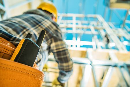 Construction Site Communication. Walkie-Talkie Radio Device in Contractors Tools Belt. Closeup Photo. Stock Photo