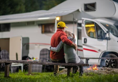 RV Campsite Family Time. Father Hugging His Daughter on Wooden Bench in Front of Campfire and Motorhome. Stock Photo