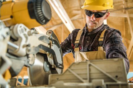 Caucasian Construction Contractor in His 30s Working with Power Tool. Powerful Circular Wood Saw. Industrial Theme.