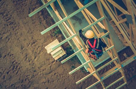 Wooden Roof Frame Building. Caucasian Roofer Working at Height. Industrial Theme.