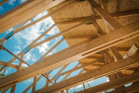House Building. Covering Wooden Roof Structure with Plywood Boards. Closeup Photo. Construction Industry. Stock Photo
