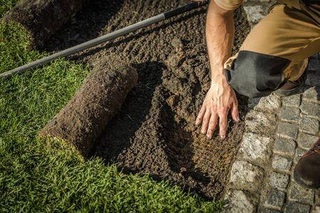 Underground Fencing and Grass Installation in a Garden. Caucasian Gardener. Agriculture Industry.
