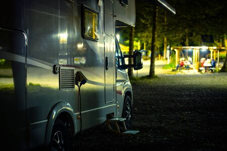 RV Camping at Night. Motorhome Campsite. Recreational Vehicle Class C. Summer Vacation.