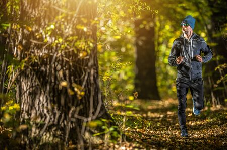Afternoon Running Activity. Caucasian Men in His 30s Running Through the Scenic Fall Time Forest.
