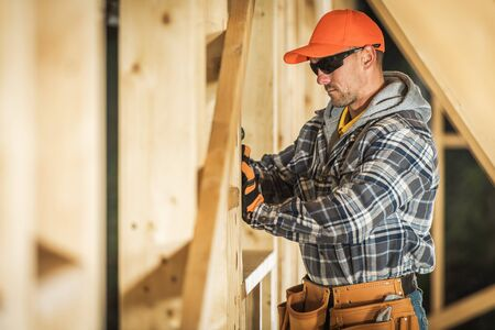 Caucasian Construction Contractor in His 30s and Wood Structure Building. House Wooden Frame. Industrial Theme.