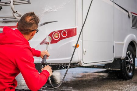 Caucasian Men in His 30s Cleaning Outside His RV Camper Van Using Pressure Washer.