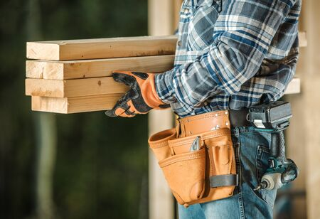 Caucasian Construction Contractor With Wood Beams. Closeup Photo.