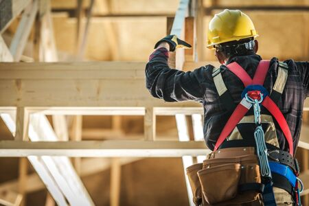Wood Construction Worker. Caucasian Builder Wearing Safety Harness and the Wooden House Structure. Industrial Theme.