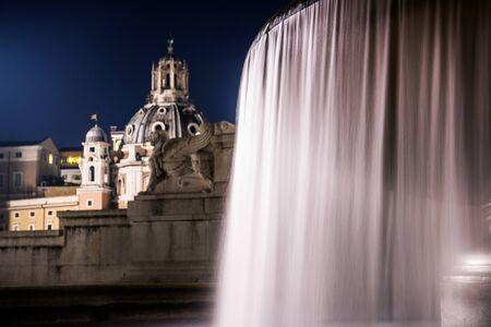 City of Rome Fountains at Night. Famous Fountain of the Tyrrhenian, Piazza Venezia. Italian Architecture. Altar of the Fatherland. Vittorio Emanuele II. Stock Photo