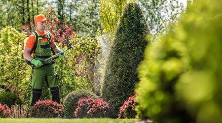 Garden Plants Pesticide. Caucasian Professional Gardener with Fertilizer. Seasonal Garden Maintenance.