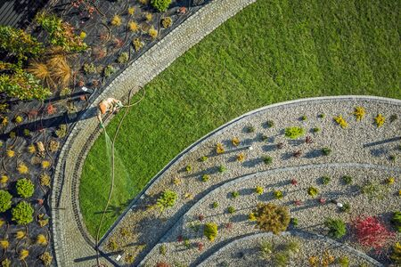 Building Backyard Garden. Landscaping and Gardening Industry. Caucasian Gardener with Hose Watering Newly Installed Natural Grass Turfs. Aerial Photo. Standard-Bild