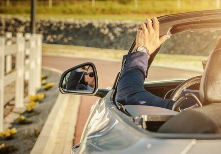 Caucasian Men in His 30 Drive His Modern Convertible Car. Hot Summer Day Road Trip.
