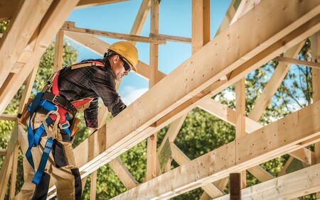 Wood House Frame Construction. Industrial Theme. Caucasian Contractor Worker.