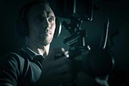DSLR Rig Videography Film Camera Caucasian Operator with Headphones. Modern Video Creator.