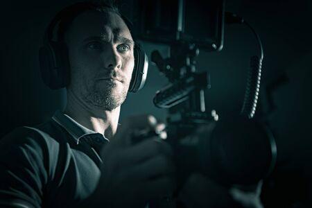 Operador caucásico de cámara de película de videografía DSLR Rig con auriculares. Creador de video moderno.