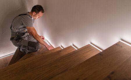 Entrepreneur d'escaliers et de garde-corps finissant des escaliers résidentiels en bois avec éclairage LED. Thème de l'amélioration de l'habitat.