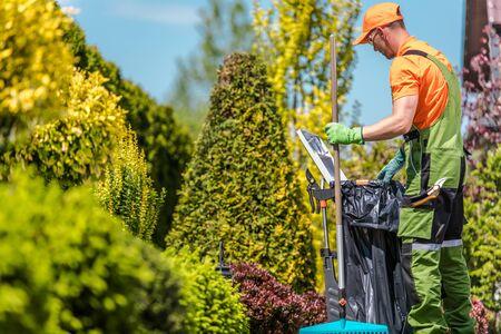 Jardinero con sus herramientas de jardín y el mantenimiento estacional. Hombres caucásicos de unos 30 años. Foto de archivo