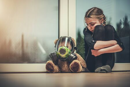 Virus Outbreak Theme. Caucasian Girl Protected Her Teddy Bear with Safety Breathing Biochemical Mask. Seating Together on a Floor Awaiting End of Pandemic.