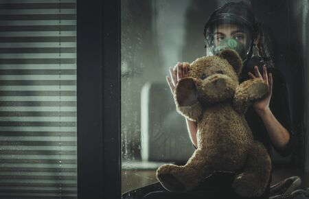 Sad Caucasian Girl Seating with Her Teddy Bear Inside Home with Biochemical Protective Mask and Looking Outside the Window. Dangerous Virus Pandemic Concept Photo.