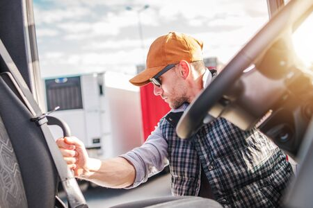 Cargo Transportation Theme. Caucasian Trucker Driver in His 30s Living His Semi Truck Cabin.