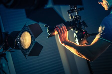 Caucasian Video Camera Operator in His 30s Taking Apartment Interior Shoots Using Blue and Orange Artificial Lighting.
