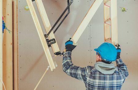 Caucasian Handyman Assembles Attic Access Wooden Ladder. 스톡 콘텐츠