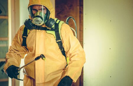Worker in Hazmat Suit and Full Face Mask Spraying Disinfection Liquid in Order to Kill Bacteria and Viruses Inside Building. Stock Photo