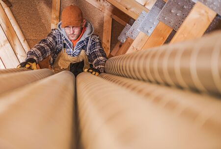 Industrial Theme. Residential Air Ventilation Pipelines Prepared by Caucasian Technician Worker. Home Air Quality. Stock Photo