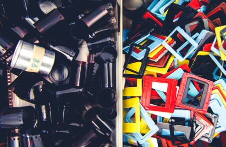 Two Larger Bins Filled With 35mm Negative Film Rolls Silver Containers And Colorful Plastic Slide Mounts.
