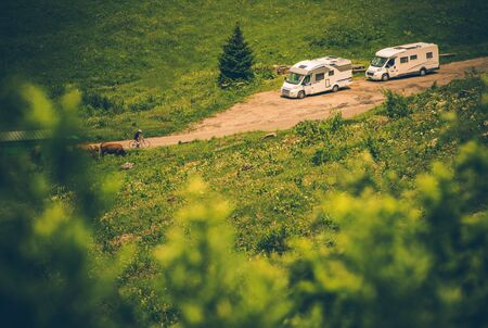 Two White Medium Size Recreational Vehicles Parked On Side Of Rural Dirt Road.