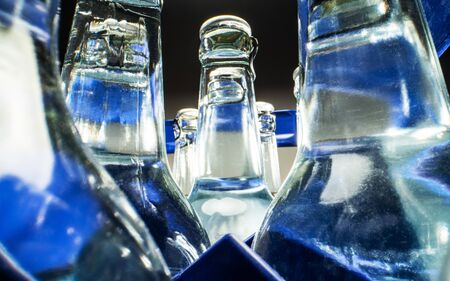 Close Up Of Blue Case Of Transparent Glass Bottles Filled With Mineral Water.