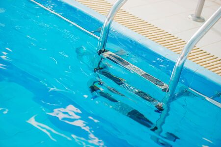 Close Up Of Silver Stainelss Steel Pool Ladder Submerged In Clean Swimming Pool Water. Banco de Imagens