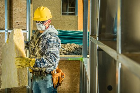 Caucasian Contractor Worker in Safe Breathing Mask and Hard Hat Working Inside Developed Building. Moving Mineral Wool Insulation. Construction Industry Safety. 스톡 콘텐츠 - 147922741