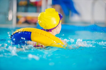 Water Sports and Recreation Theme. Young Girl Swimming in the Large Indoor Pool Inside Yellow Inflatable Tube. Wearing Swim Cap and Goggles.