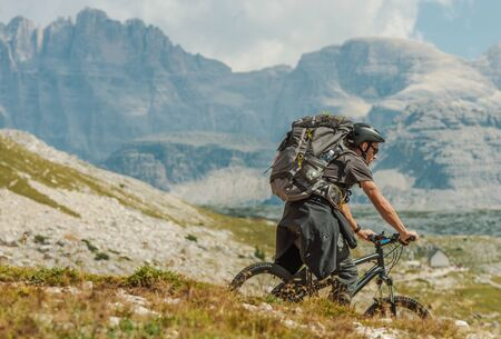 Caucasian Biker in His 30s Wearing Large Backpack Riding on the Mountain Trail in Italian Dolomites near Misurina, Italy. Outdoor Sports and Recreation Theme. Summer Season o n a Bike. 스톡 콘텐츠