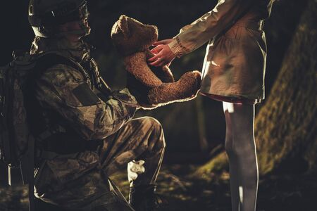 Army and Patriotism Theme. Soldier Giving Teddy Bear Toy to Caucasian Girl in Dark Foggy Forest