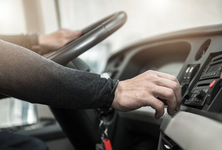 Public Transportation Concept. Caucasian Coach Bus Driver Keeping Steering Wheel and Changing Radio Station Close Up Photo.